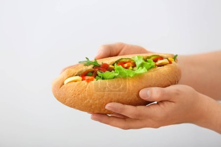 Female hands with tasty hot dog on light backgroun...