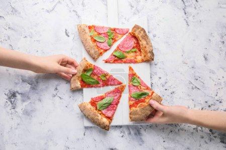 Photo pour Femmes prenant des tranches de savoureuse pizza à bord sur fond blanc - image libre de droit