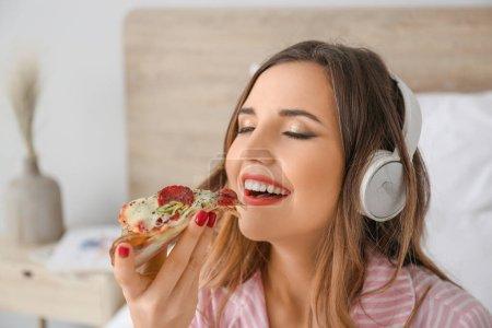 Photo pour Matin de belle jeune femme mangeant de savoureuses pizzas et écoutant de la musique en chambre à coucher - image libre de droit