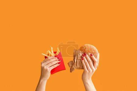 Photo pour Female hands with french fries and burger on color background - image libre de droit