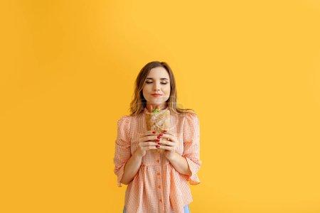 Photo pour Portrait d'une belle jeune femme avec hot dog français sur fond coloré - image libre de droit