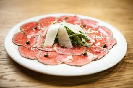 Photo for Black angus beef carpaccio with parmesan cheese on a plate - Royalty Free Image