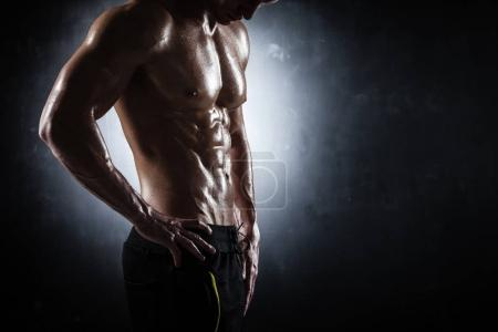 Photo for Handsome athletic man posing on black background - Royalty Free Image