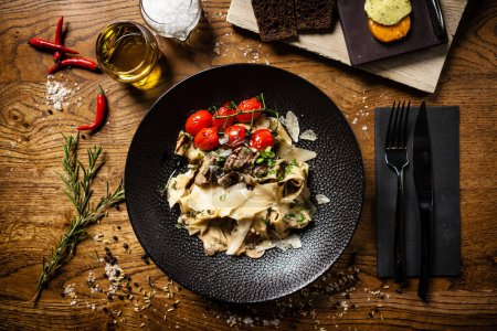 Photo for Black Angus pappardelle pasta with beef, champignon and parmegano cheese - Royalty Free Image