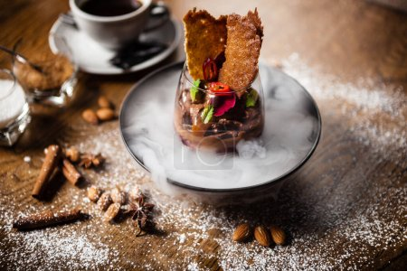 Photo for Chocolate mousse with coffee liquor, cherry, kama biscuit served in liquid ice smoke - Royalty Free Image