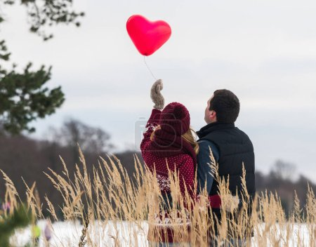 Photo pour Vue arrière du jeune homme et de la jeune femme debout avec des ballons en forme de cœur dans la nature hivernale. - image libre de droit