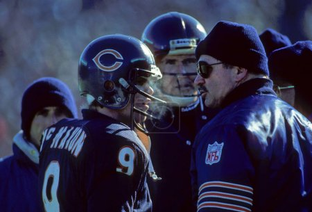 Quarterback Jim McMahon and Coach Mike Ditka on the sidelines going over the next play.