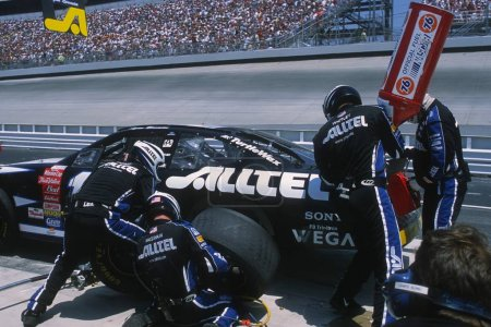 Pit Crews work on cars during a NASCAR race.
