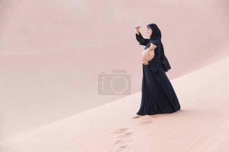 Photo pour Belle femme dans un abaya noir dans le désert avec une amphore traditionnelle arabe de l'eau . - image libre de droit