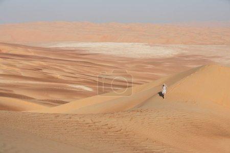 Photo pour Jeune femme en robe d'été marchant sur les dunes du désert. Abu Dhabi, Émirats arabes unis . - image libre de droit