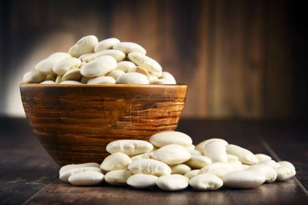 Composition with bowl of white beans on wooden table