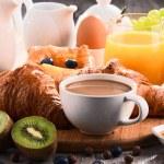 Постер, плакат: Breakfast served with coffee juice croissants and fruits