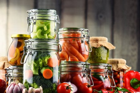 Jars with marinated food and organic raw vegetables