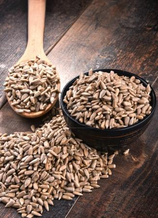 Composition with bowl of shelled sunflower seeds on wooden table