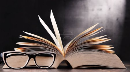 Composition with open book and glasses on the tabl...
