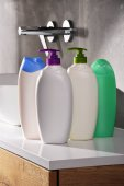 Plastic bottles of body care and beauty products in the bathroom