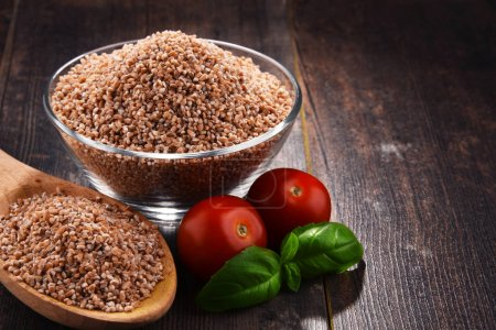 Bowl of uncooked spelt on wooden table