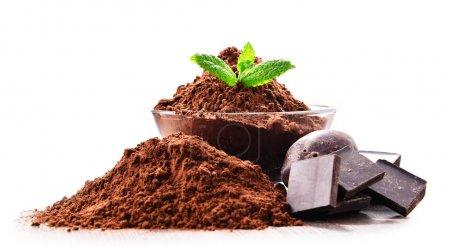 Zusammensetzung mit einer Schüssel Kakaopulver isoliert auf weiß