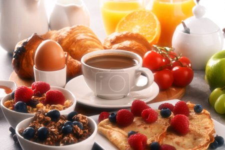 Photo for Breakfast served with coffee, orange juice, croissants, egg, cereals and fruits. Balanced diet. - Royalty Free Image