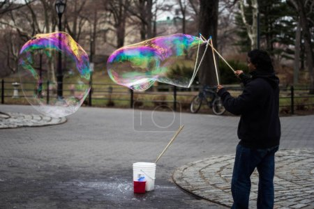 NEW YORK, USA - APRIL 2014: Indian man inflating huge soap bubbles at Central Park, NY.