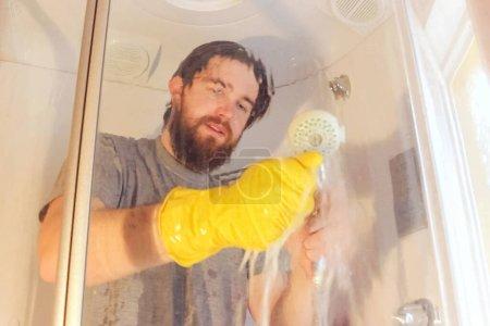 Foto de La limpieza sanitaria de la cabina de ducha para la seguridad durante el coronavirus.man en una camiseta gris y barba, desinfecta el cuarto de baño utilizando guantes químicos amarillos y agento.immune es la garantía de salud. - Imagen libre de derechos