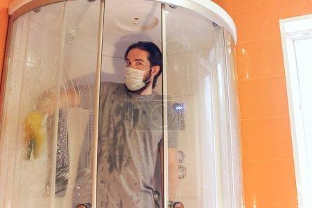 Foto de Limpieza sanitaria de la cabina de ducha para la seguridad del hogar durante la coronavirus.Un hombre en una camiseta gris y barba, usando una máscara desechable, desinfecta el cuarto de baño utilizando guantes químicos amarillos y agentes de limpieza. - Imagen libre de derechos
