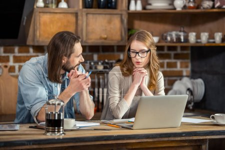 Photo for Beautiful young couple working with papers and laptop at home - Royalty Free Image