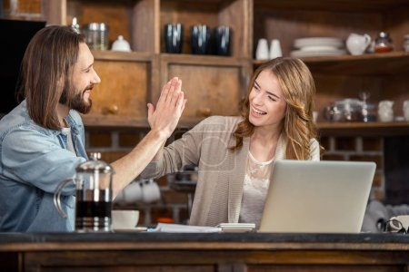 Photo for Couple giving high five while working together with laptop at home - Royalty Free Image