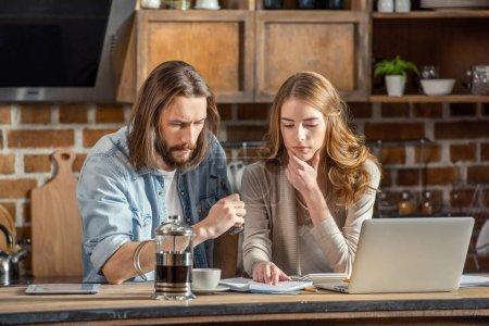 Photo pour Jeune couple travaillant ensemble avec des papiers et un ordinateur portable à la maison - image libre de droit