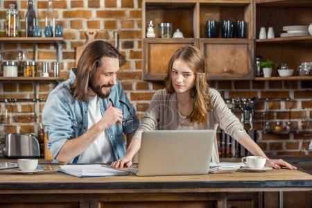 Photo for Attractive smiling couple using laptop while working together at home - Royalty Free Image