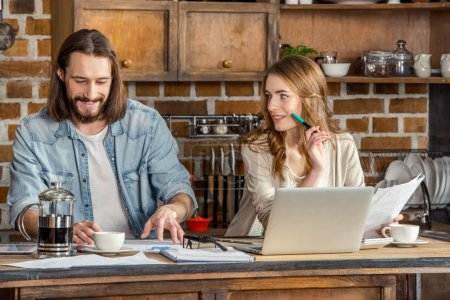 Photo for Beautiful young couple working with documents and laptop at home - Royalty Free Image