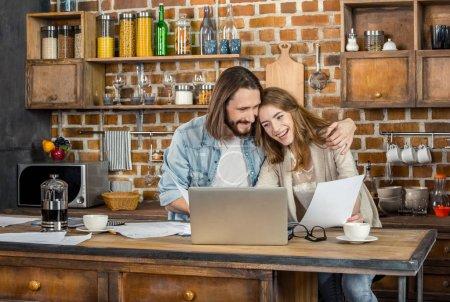 Photo pour Couple travaillant avec un ordinateur portable tout en restant debout dans la cuisine - image libre de droit