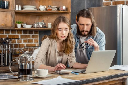 Young pensive couple working in kitchen while usin...