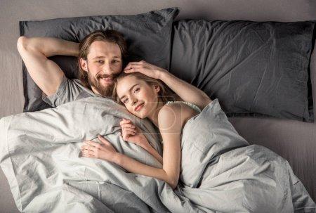 Photo pour Vue aérienne du jeune couple heureux amoureux couché au lit - image libre de droit