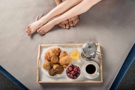 Photo for Partial top view of male and female legs and breakfast on bad tray - Royalty Free Image