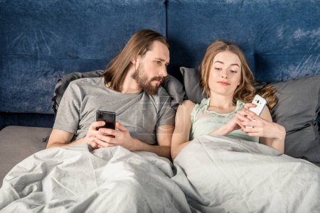Photo for Man peeking at smartphone of his girlfriend while they lying in bed - Royalty Free Image