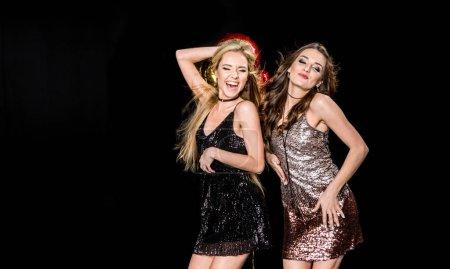 Photo pour Superbes jeunes femmes en robes scintillantes dansant isolées sur noir - image libre de droit
