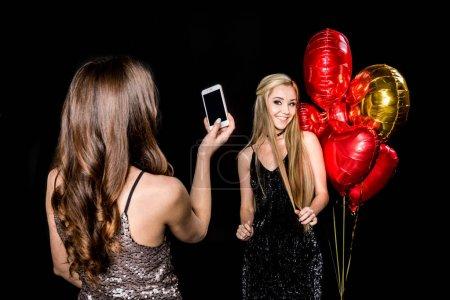 Woman photographing beautiful friend