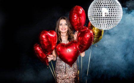 Photo for Beautiful young woman posing with shiny balloons and smiling at camera isolated on black - Royalty Free Image