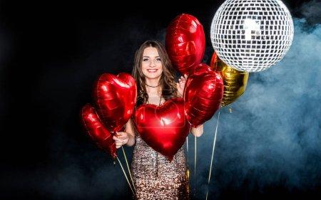 Photo pour Belle jeune femme posant avec des ballons brillants et souriant à la caméra isolée sur noir - image libre de droit