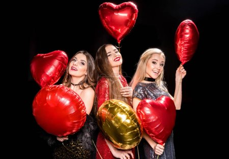 Photo pour Gorgeous young women in glittering dresses posing with shiny balloons  isolated on black - image libre de droit