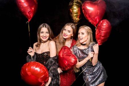 Photo pour Magnifiques jeunes femmes posant avec des ballons rouges et dorés en forme de coeur isolés sur noir - image libre de droit