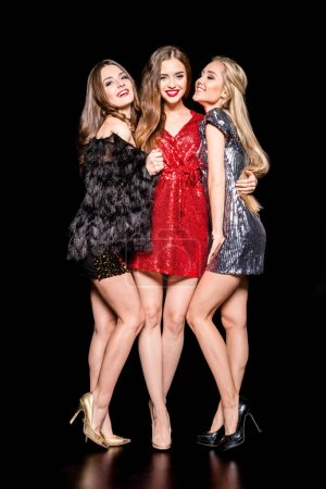 Photo for Three young beautiful women in stylish dresses standing embracing  isolated on black - Royalty Free Image