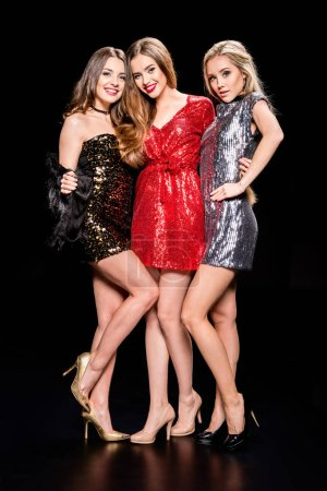 Photo pour Three young beautiful women in stylish dresses standing embracing  isolated on black - image libre de droit