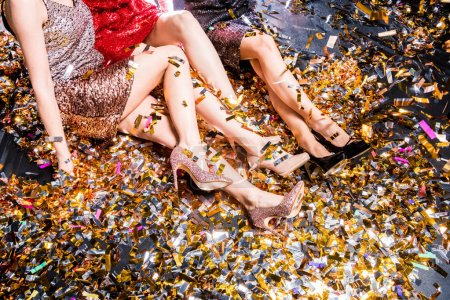 Photo for Partial view or three women in party clothes sitting on the floor covered with confetti - Royalty Free Image