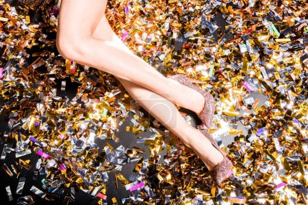 Photo for Partial view of female legs in fashion high heel shoes on confetti background - Royalty Free Image