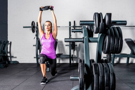 Photo for Athletic young woman doing exercise with barbell plate in gym - Royalty Free Image