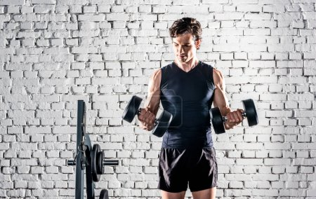 Photo for Young sportive man in sportswear exercising with dumbbells in gym - Royalty Free Image