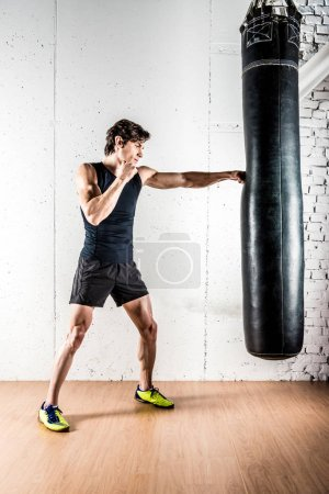 Kickboxer boxing in punching bag