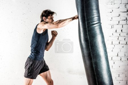 Photo for Muscular male kickboxer in sportswear boxing in punching bag - Royalty Free Image